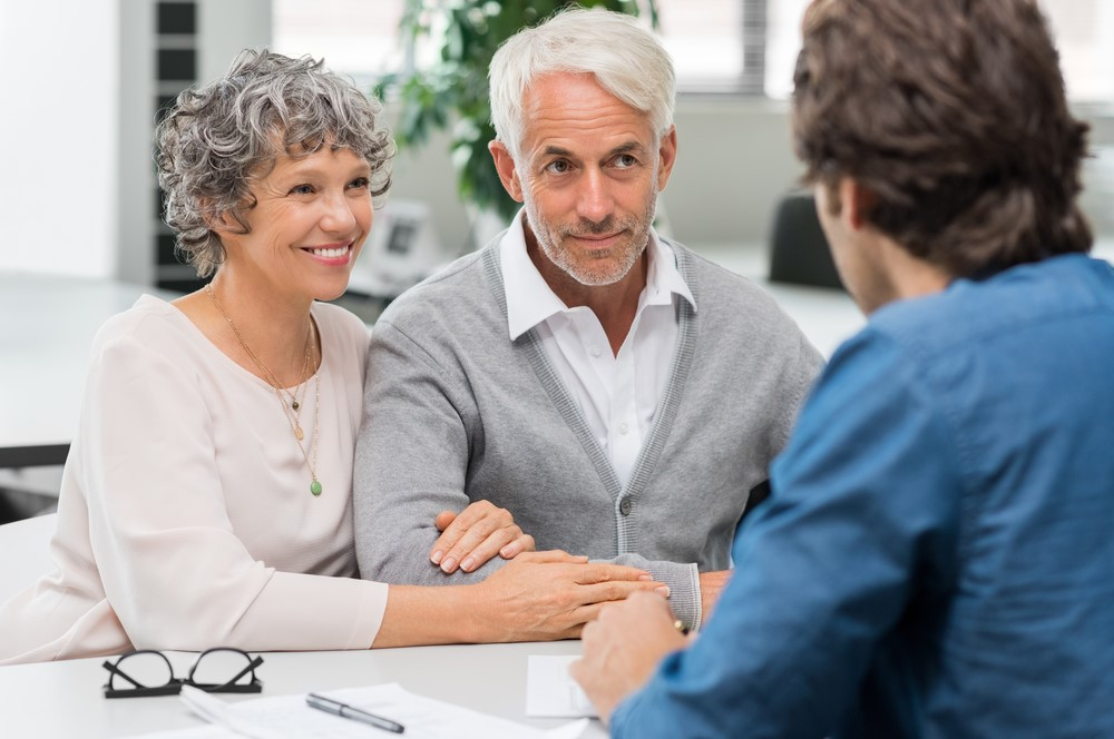 A husband and wife speaking with a long-term care insurance agent about their policy options