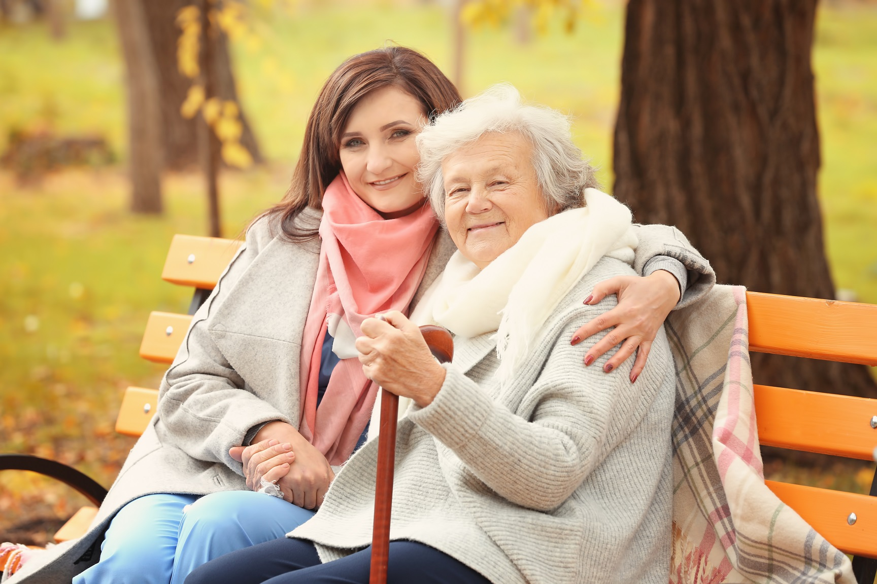 Daughter sitting with her elderly mother on a park bench.